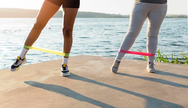 Вид спереди подруг, вместе тренирующихся на берегу озера