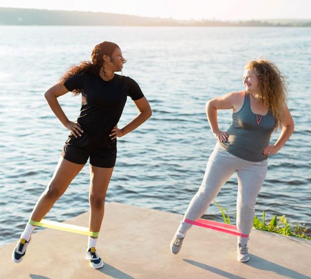 Вид спереди подруг, тренирующихся на берегу озера
