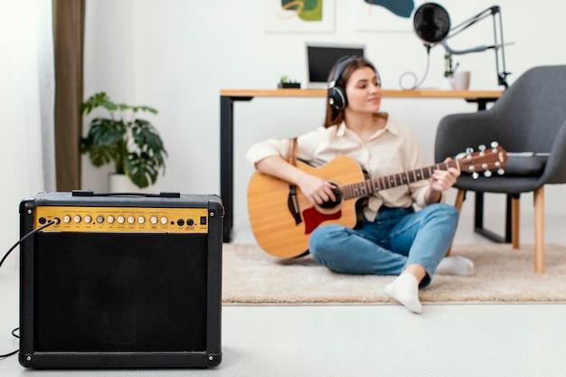 Вид спереди музыканта, играющего на акустической гитаре дома