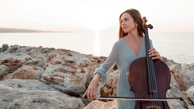 Вид спереди женского музыканта, играющего на виолончели