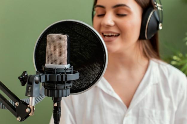마이크에 노래하는 여성 음악가의 전면보기