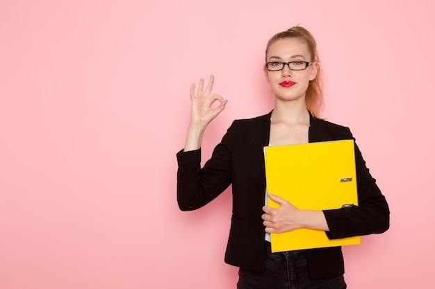 淡いピンクの壁に書類を保持している黒の厳格なジャケットの女性サラリーマンの正面図