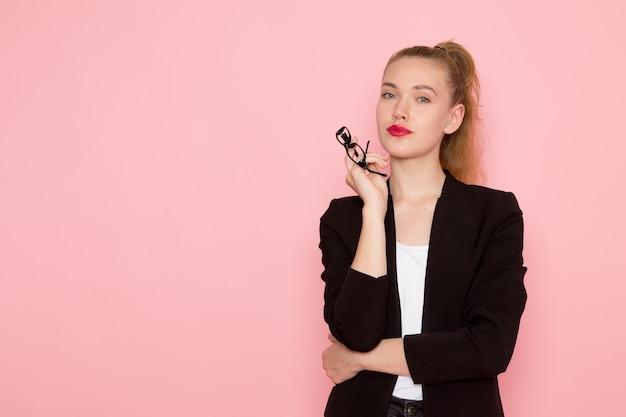 밝은 분홍색 벽에 그녀의 광학 선글라스를 들고 검은 엄격한 재킷에 여성 회사원의 전면보기