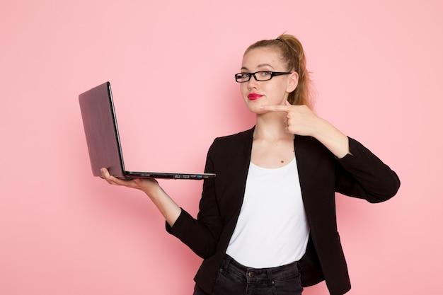 밝은 분홍색 벽에 노트북을 사용하여 들고 검은 엄격한 재킷에 여성 회사원의 전면보기