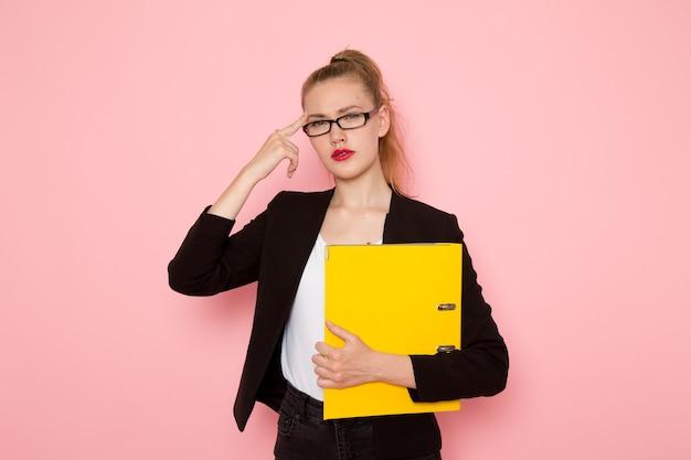 분홍색 벽에 노란색 문서를 들고 검은 엄격한 재킷에 여성 회사원의 전면보기