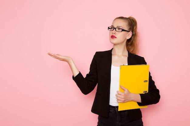 밝은 분홍색 벽에 노란색 파일을 들고 검은 엄격한 재킷에 여성 회사원의 전면보기