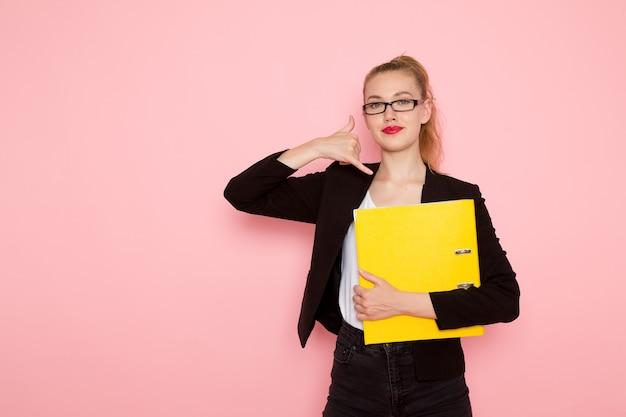 淡いピンクの壁に笑みを浮かべて黄色のファイルを保持している黒の厳格なジャケットの女性サラリーマンの正面図