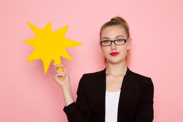 밝은 분홍색 벽에 노란색 기호를 들고 검은 엄격한 재킷에 여성 회사원의 전면보기