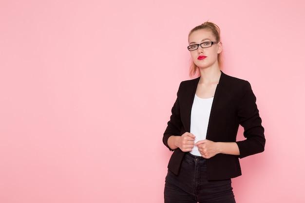 분홍색 벽에 포즈를 취하는 검은 엄격한 재킷에 여성 회사원의 전면보기