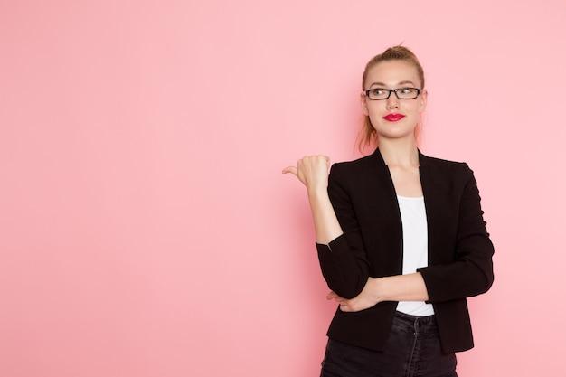 밝은 분홍색 벽에 포즈와 미소 검은 엄격한 재킷에 여성 회사원의 전면보기