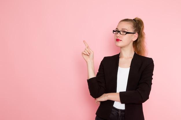 분홍색 벽에 포즈 검은 엄격한 재킷에 여성 회사원의 전면보기