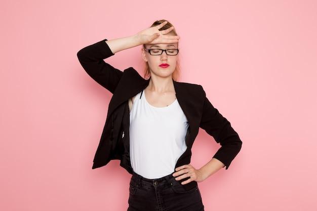 ピンクの壁にポーズをとって黒の厳格なジャケットの女性サラリーマンの正面図
