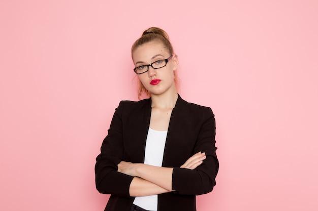 밝은 분홍색 벽에 불쾌한 표정으로 포즈를 취하는 검은 엄격한 재킷에 여성 회사원의 전면보기
