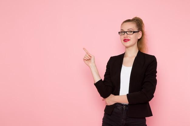 검은 엄격한 재킷 미소하고 분홍색 벽에 포즈를 취하는 여성 회사원의 전면보기