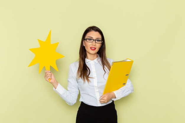 녹색 벽에 큰 노란색 기호 및 파일을 들고 흰 셔츠와 검은 치마에 여성 회사원의 전면보기