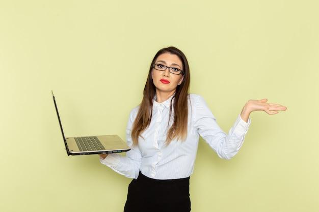 Вид спереди офисного работника в белой рубашке и черной юбке, держащего и использующего ноутбук на светло-зеленой стене