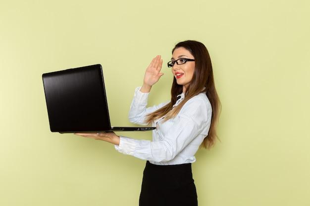 緑の壁にラップトップを保持し、使用している白いシャツと黒いスカートの女性サラリーマンの正面図