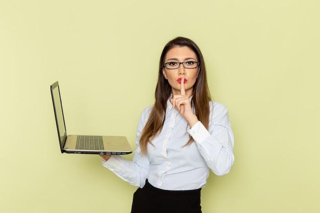 밝은 녹색 벽에 노트북을 들고 흰 셔츠와 검은 치마에 여성 회사원의 전면보기