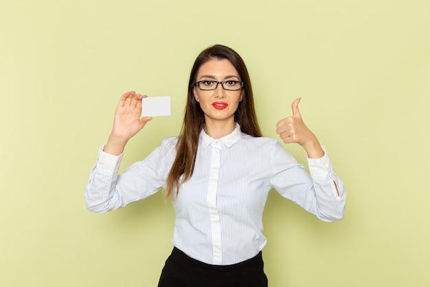薄緑色の壁にプラスチックカードを保持している白いシャツと黒いスカートの女性サラリーマンの正面図