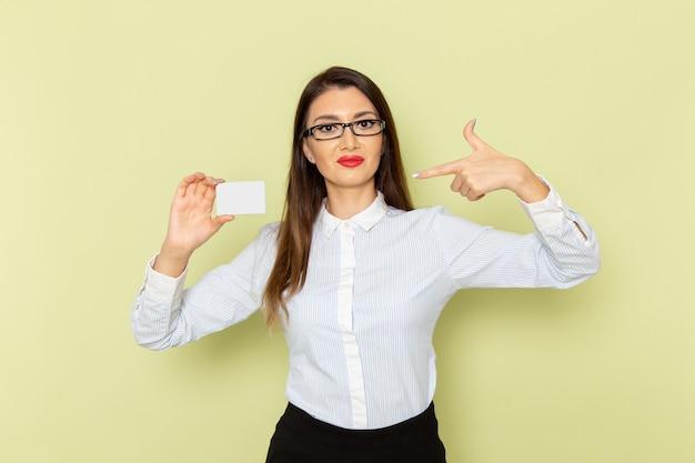 薄緑色の壁に白いカードを保持している白いシャツと黒いスカートの女性サラリーマンの正面図