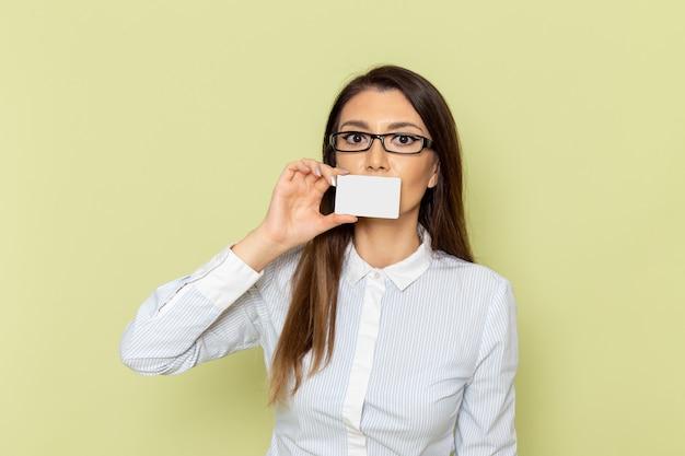 녹색 벽에 흰색 플라스틱 카드를 들고 흰 셔츠와 검은 치마에 여성 회사원의 전면보기