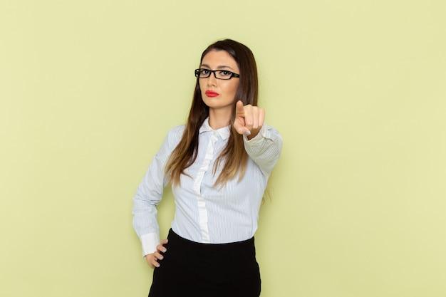 Вид спереди офисного работника в белой рубашке и черной юбке на зеленой стене