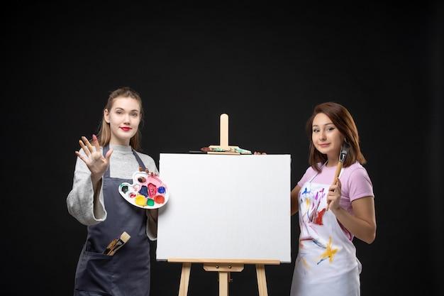 Вид спереди художников-женщин с мольбертом, держащим краски на темной стене