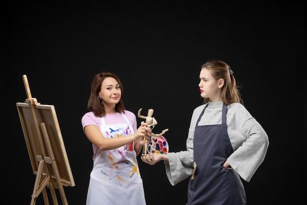 Вид спереди художников-женщин с красками и человеческой фигурой на черной стене