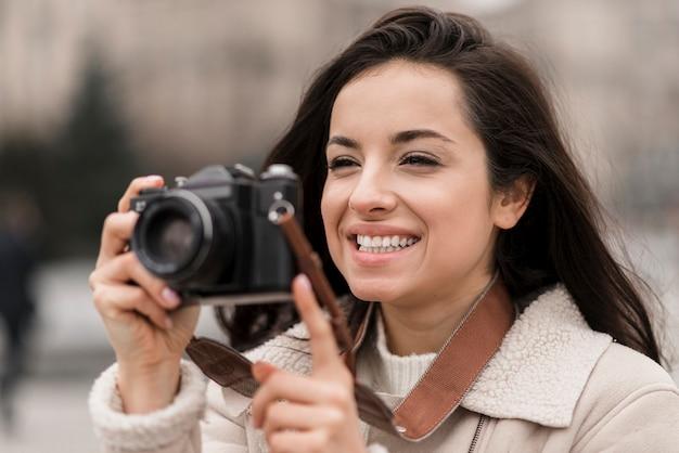 Вид спереди женского фотографа, делающего снимок
