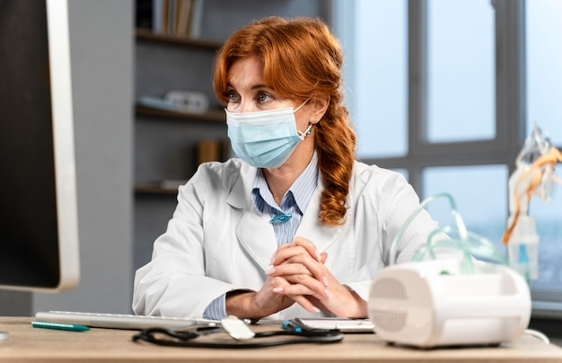 コンピューターを見ている医療マスクと彼女の机で女性医師の正面図