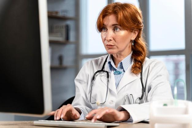 机の上のコンピューターで物事を探している女性医師の正面図