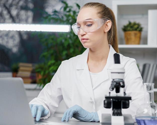 Вид спереди женщины-исследователя в лаборатории с защитными очками и микроскопом