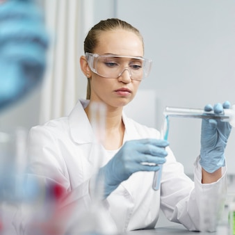 테스트 튜브 및 안전 안경이있는 실험실에서 여성 연구원의 전면보기