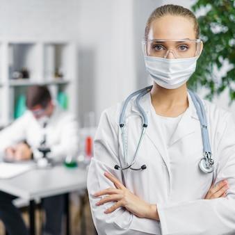 Вид спереди женщины-исследователя со стетоскопом и медицинской маской