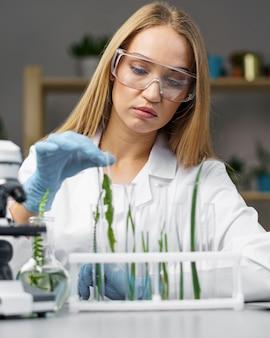 테스트 튜브 및 현미경으로 여성 연구원의 전면보기