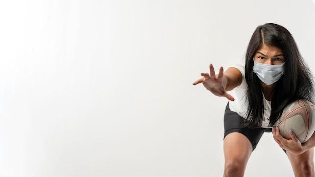 Вид спереди регби женского пола с мячом и медицинской маской