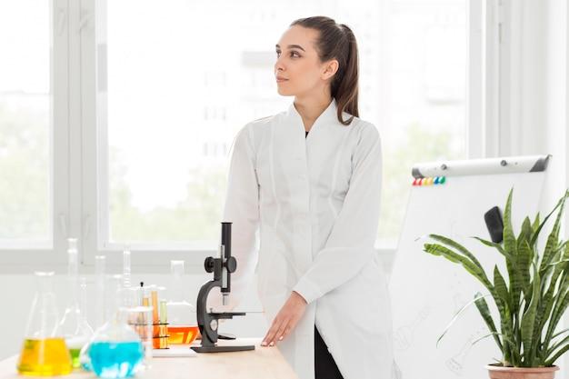 Вид спереди женского ученого, позирует рядом с микроскопом