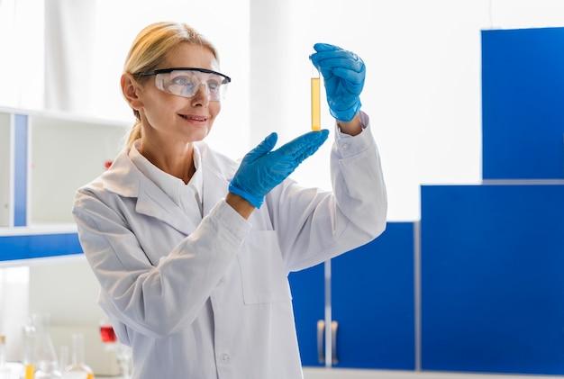Вид спереди женского ученого с хирургические перчатки, глядя на вещество