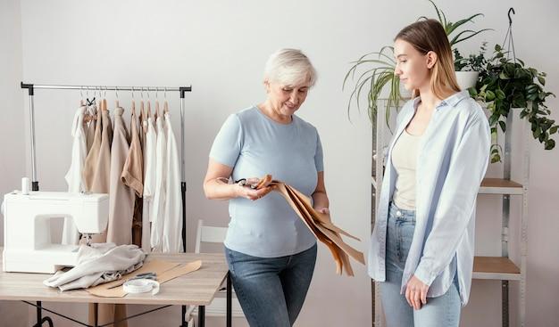 クライアントとスタジオで女性の仕立て屋の正面図