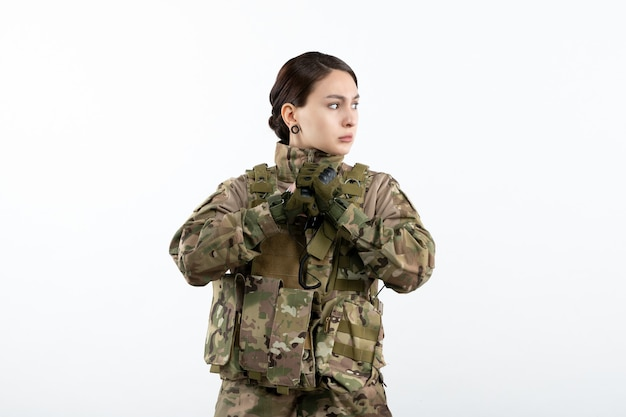 흰 벽에 위장에 여성 군인의 전면보기