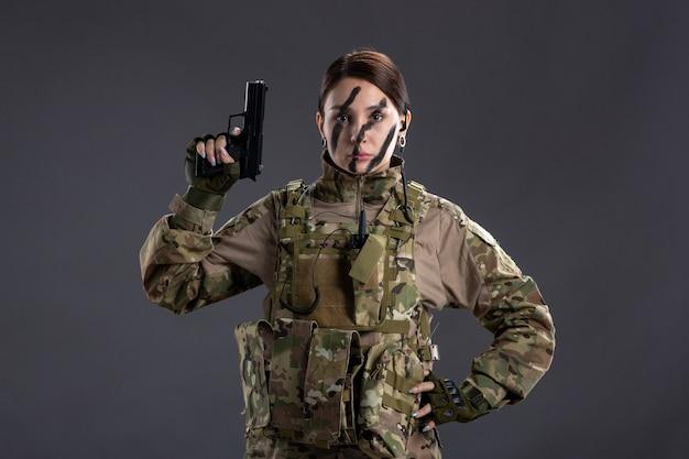 カモフラージュの暗い壁に銃を持つ女性兵士の正面図