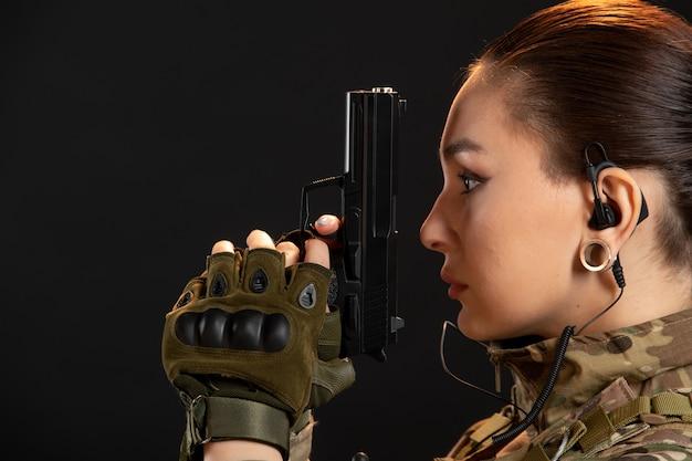黒い壁に制服を着た銃を持つ女性兵士の正面図