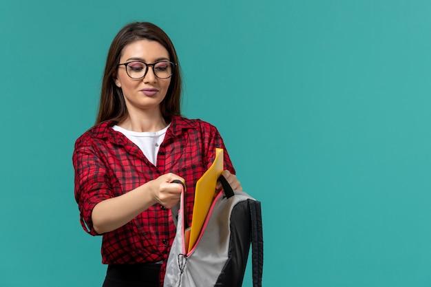 水色の壁にバックパックとファイルを保持している女子学生の正面図