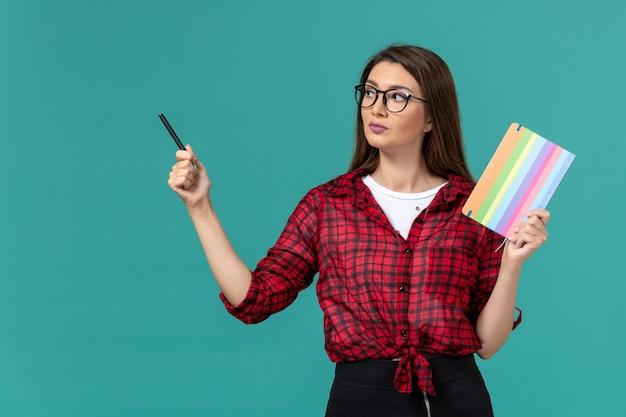 青い壁にコピーブックとペンを保持している女子学生の正面図