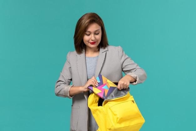 水色の壁にコピーブックを入れて黄色のバックパックを保持している灰色のジャケットの女子学生の正面図