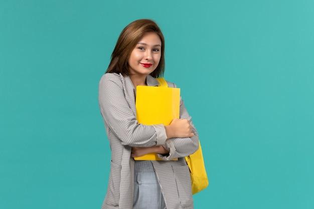 彼女の黄色のバックパックを身に着けて、水色の壁にファイルを保持している灰色のジャケットの女子学生の正面図
