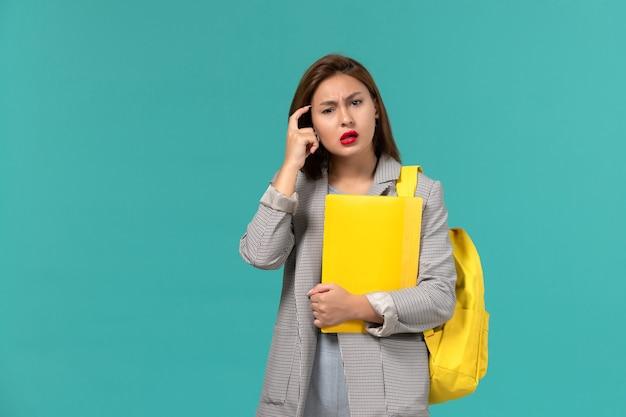 彼女の黄色のバックパックを身に着けて、水色の壁を考えてファイルを保持している灰色のジャケットの女子学生の正面図