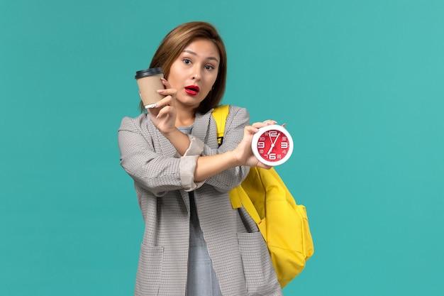 水色の壁に時計とコーヒーを保持している彼女の黄色のバックパックを身に着けている灰色のジャケットの女子学生の正面図