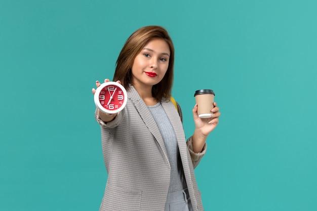 青い壁に時計とコーヒーを保持している彼女の黄色のバックパックを身に着けている灰色のジャケットの女子学生の正面図