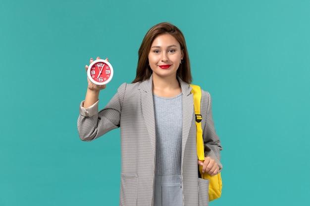 파란색 벽에 시계를 들고 그녀의 노란색 배낭을 입고 회색 재킷에 여성 학생의 전면보기